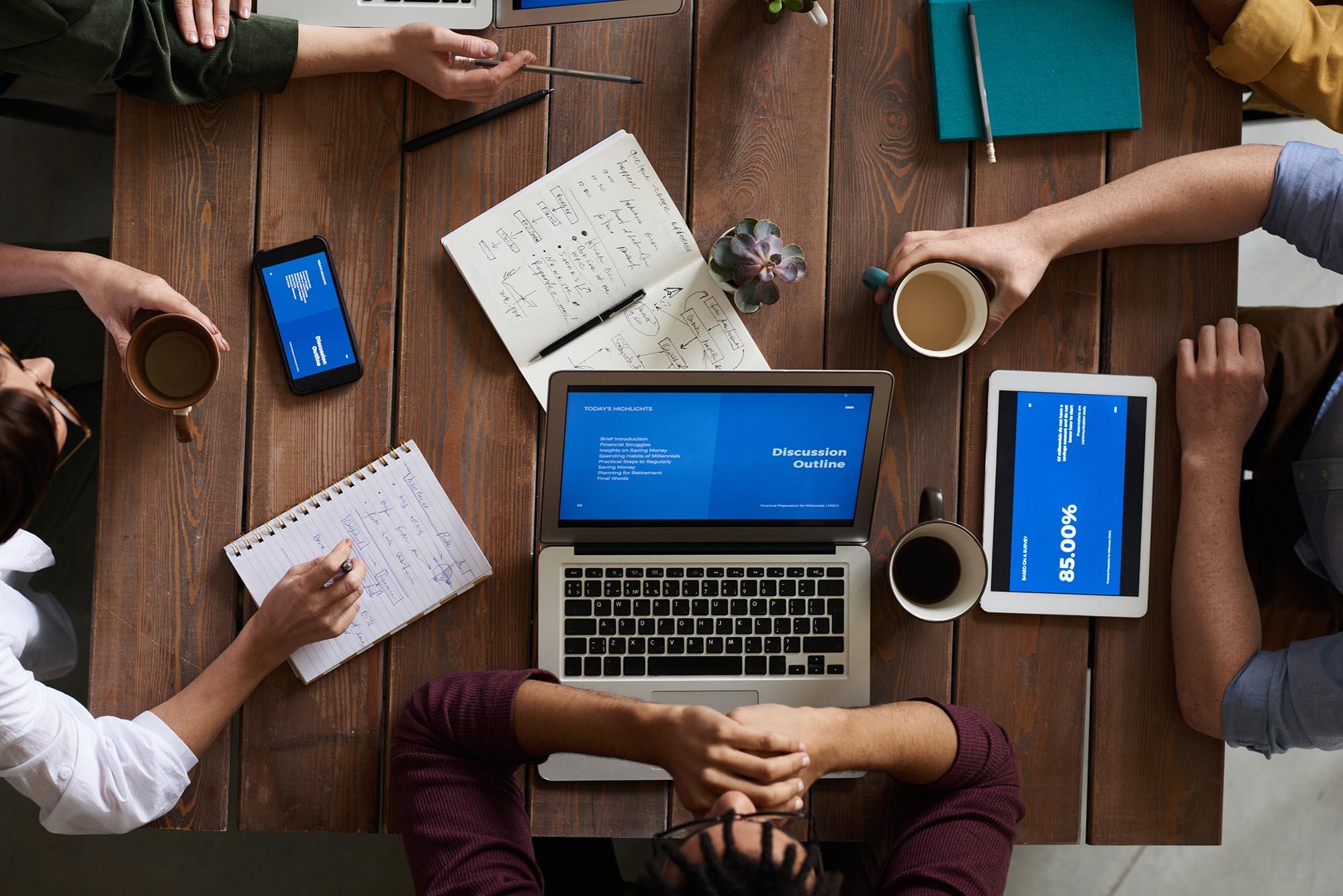 Gruppe von Menschen arbeiten an einem Tisch mit Notizbüchern und Laptops