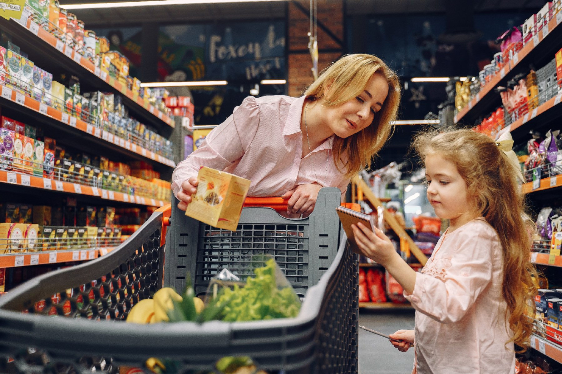 Photo of a woman with a young daughter grocery shopping together.