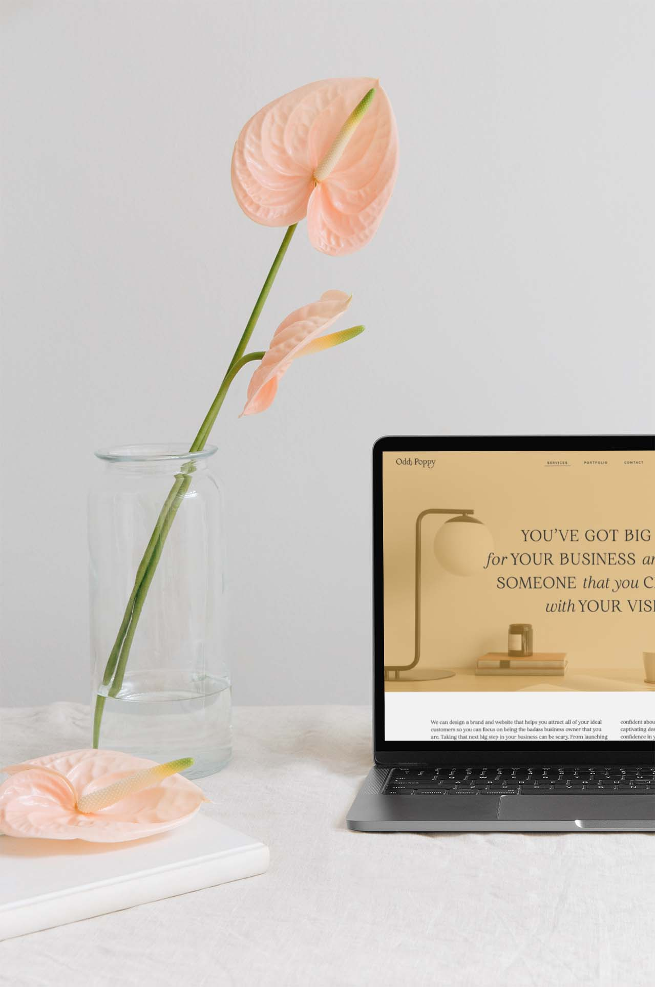 Website design by Odd Poppy Brand Co. on a slat gray Macbook Pro on a white table cloth next to a vase with a pink flower.