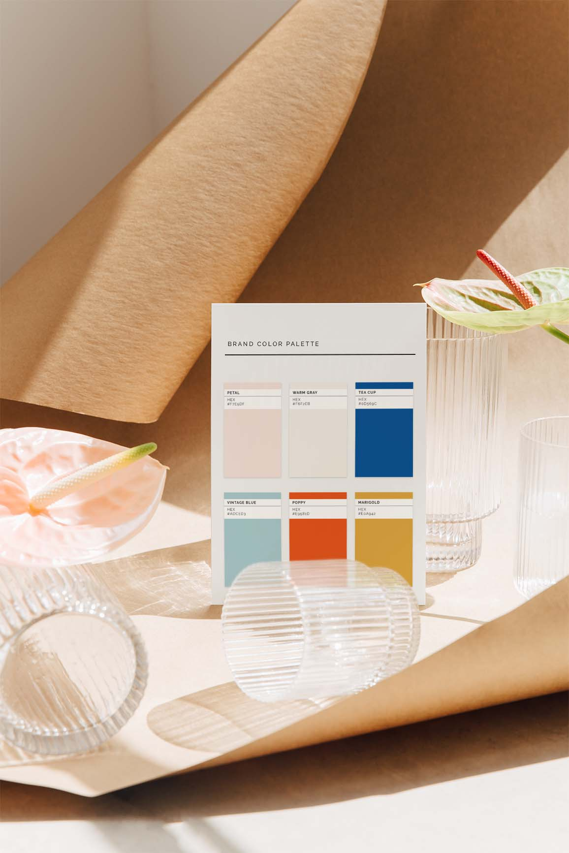 Brand color palette swatch balanced with fluted glassware and flowers.