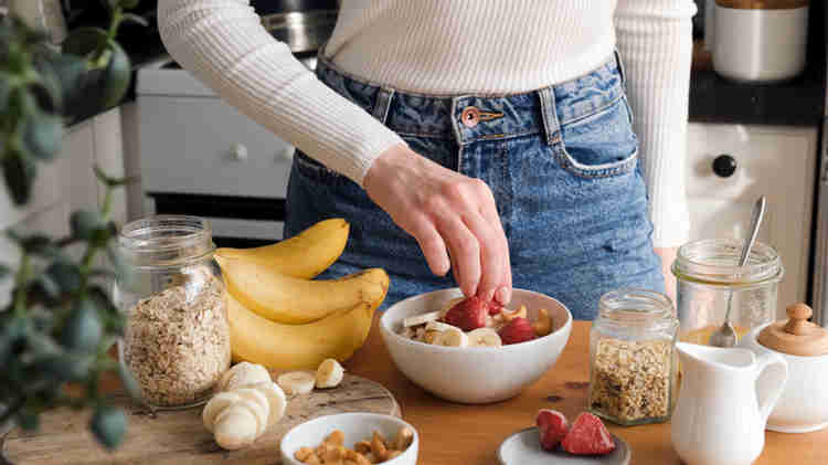 Hands eating oatmeal and other fruits