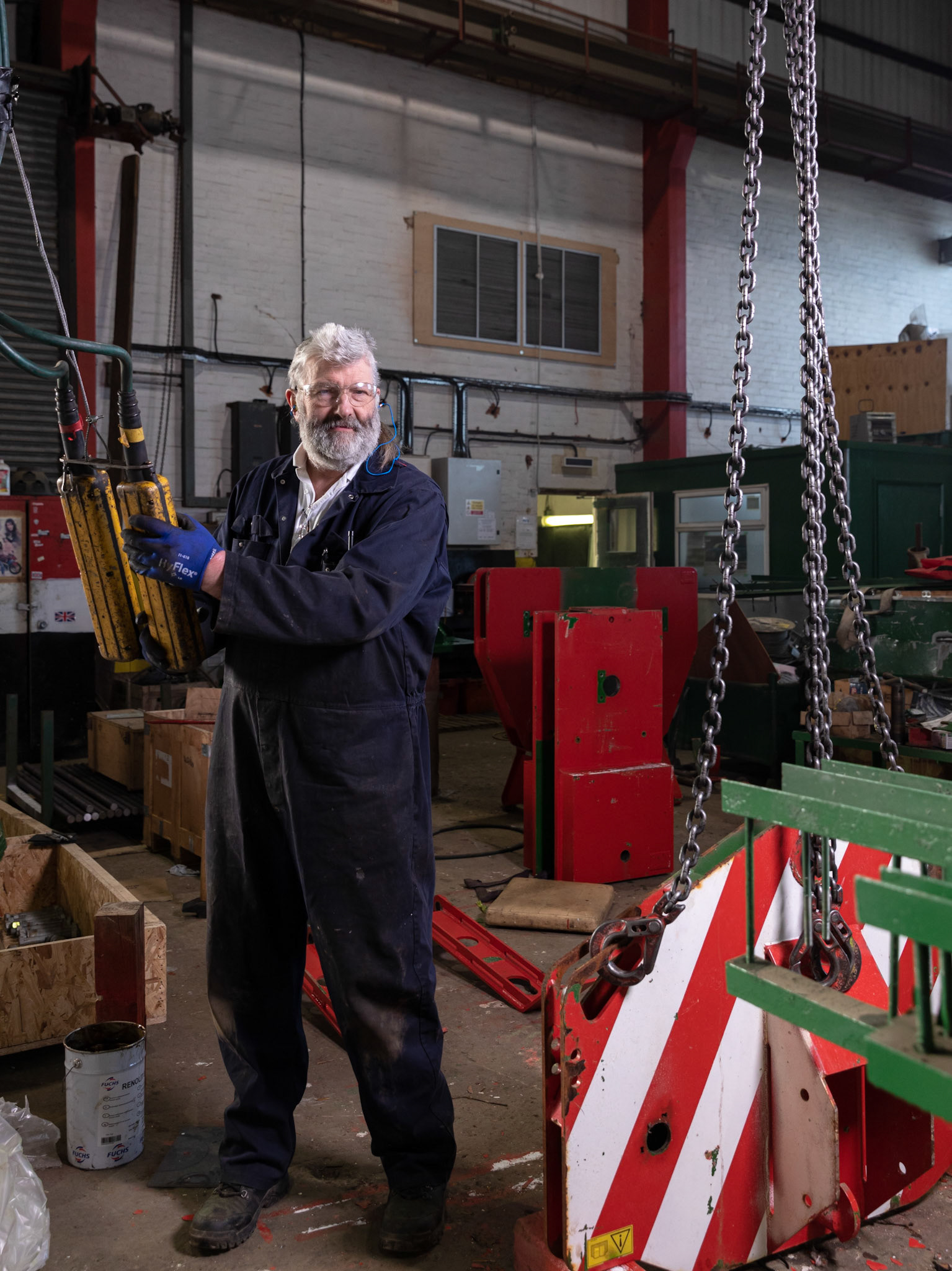 industrial portrait off worker in factory with ear plugs and chain lifting device