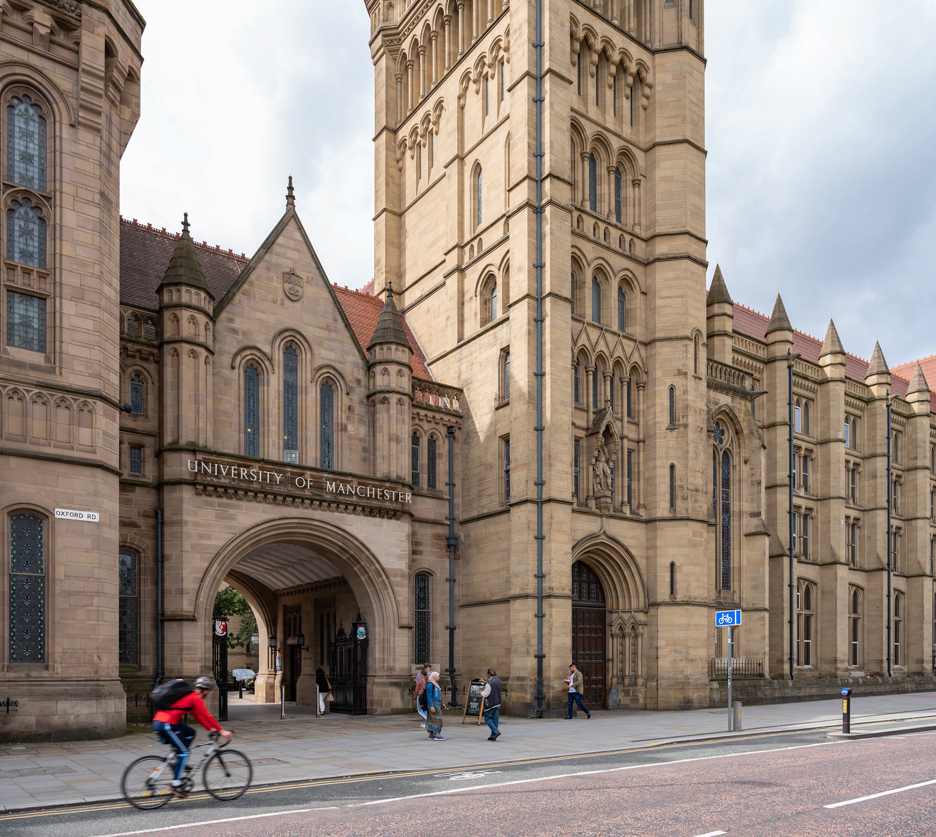 Commercial Photography University of Manchester Campus with students walking through with Brunswick building behind cloudy day