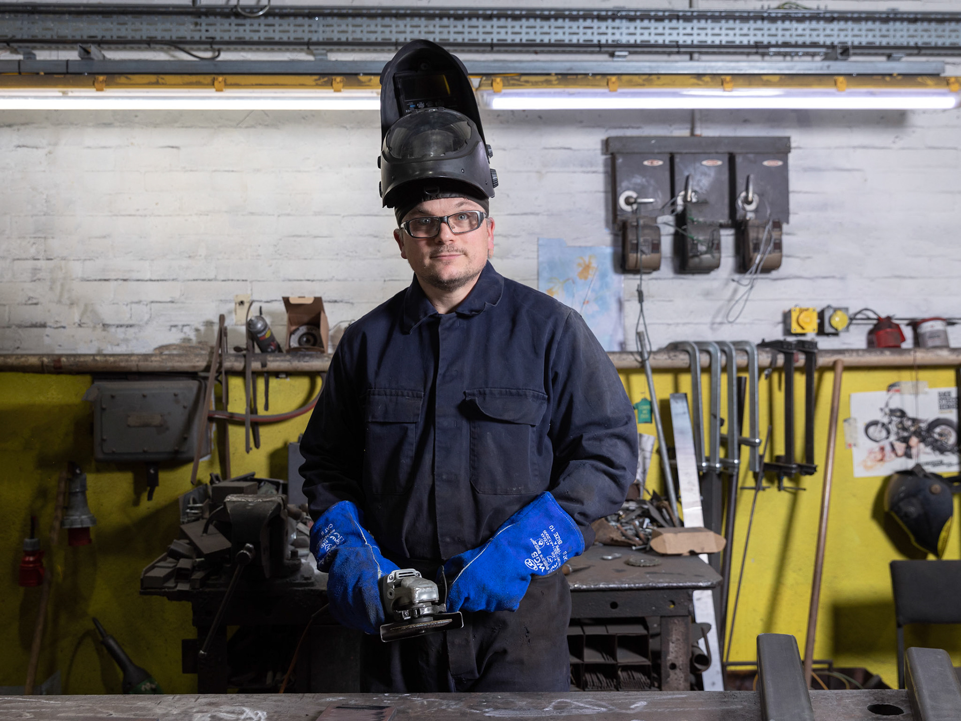 Commercial Photography Industrial Portrait steel worker with welding hat holding angle grinder