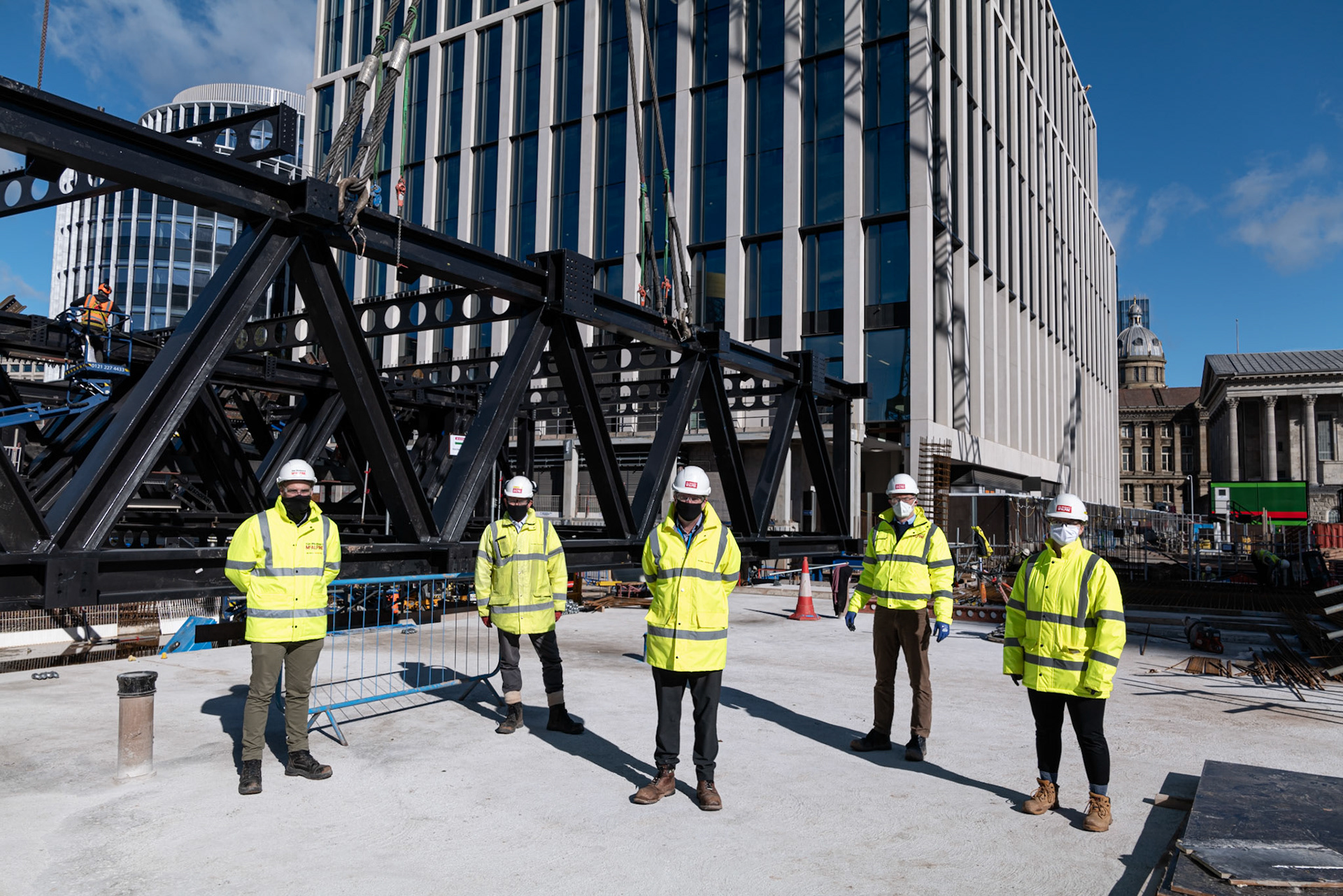 Construction Photography five staff members with covid masks and high vis in front of steel work