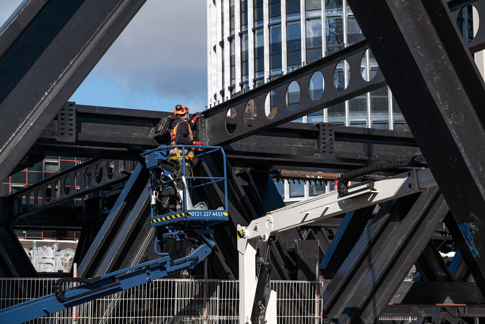 Construction Photography Metal work outside in blue sky in Birmingham detail with worker and black steel