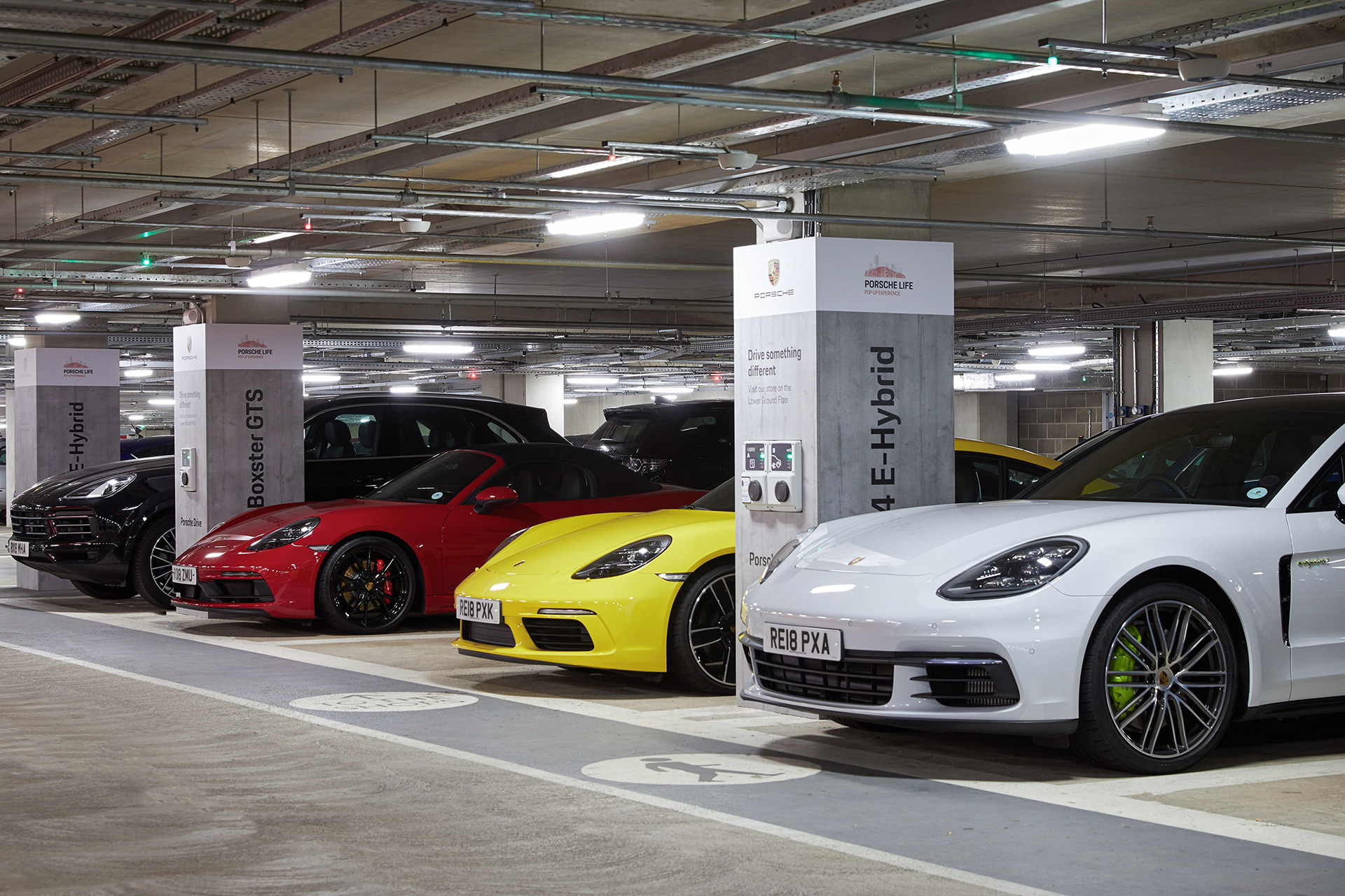 Retail Photography Porsche Store Oxford red, white and yellow Porsche cars lined up in car park for drive away experience