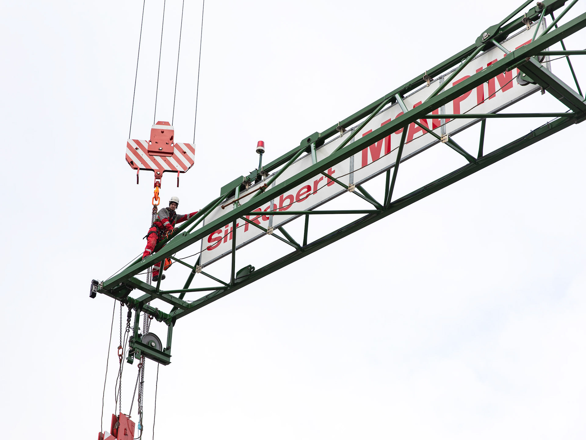 Commercial Photography at Industrial Tower Cranes the end of a crane with worker on the very end at hight
