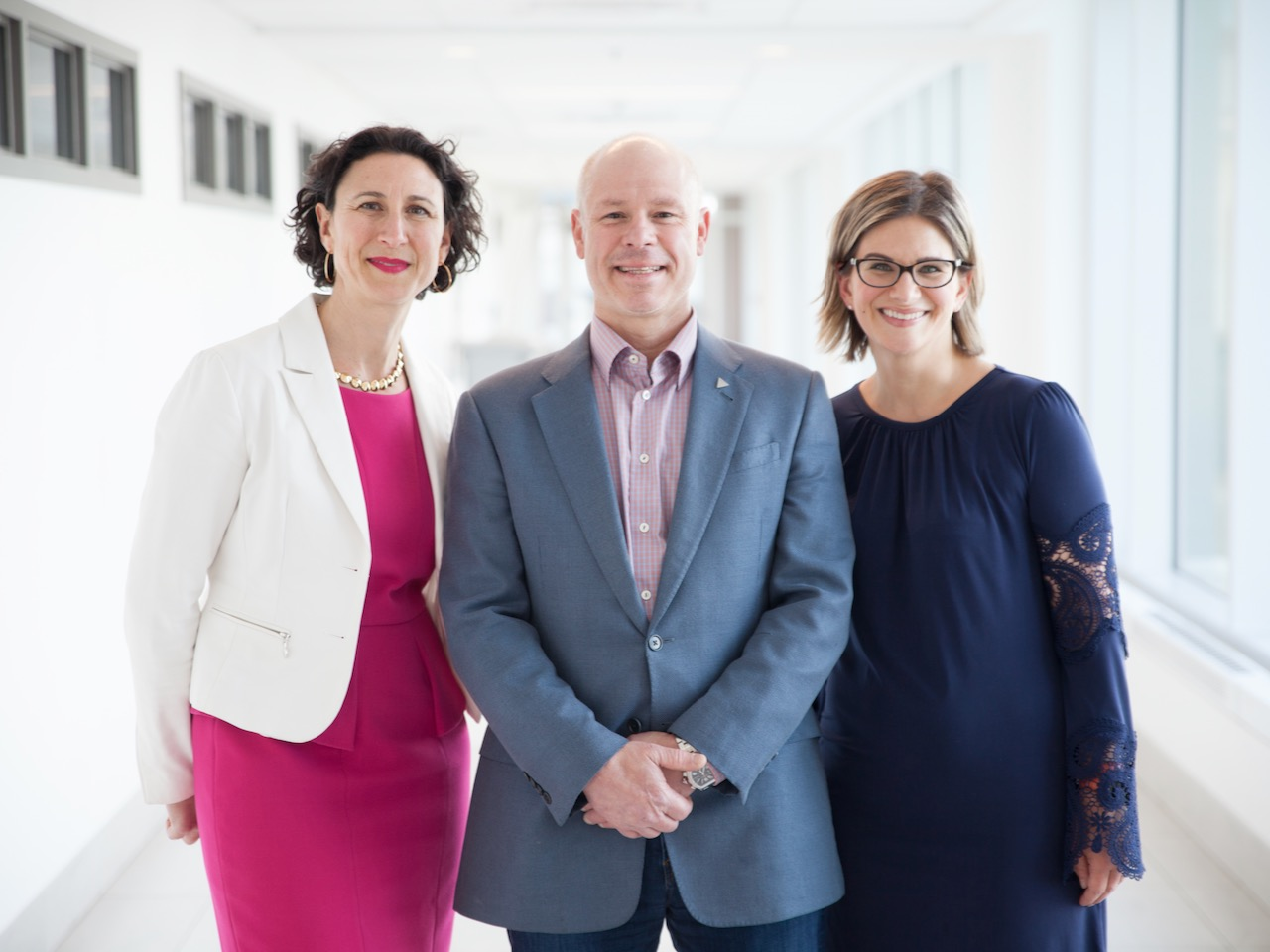 Image of three people in formal outfits posing for photo