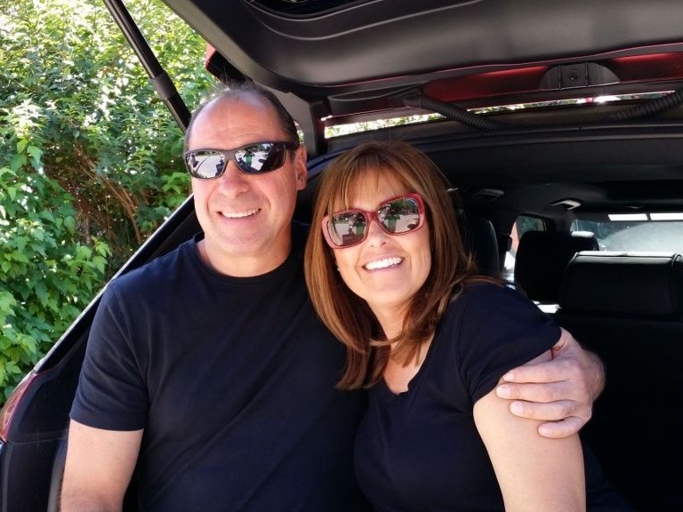 Image of man and woman smiling sitting in the back of a car