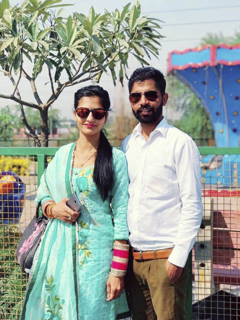 Image of couple wearing bright clothing and sunglasses posing for photo