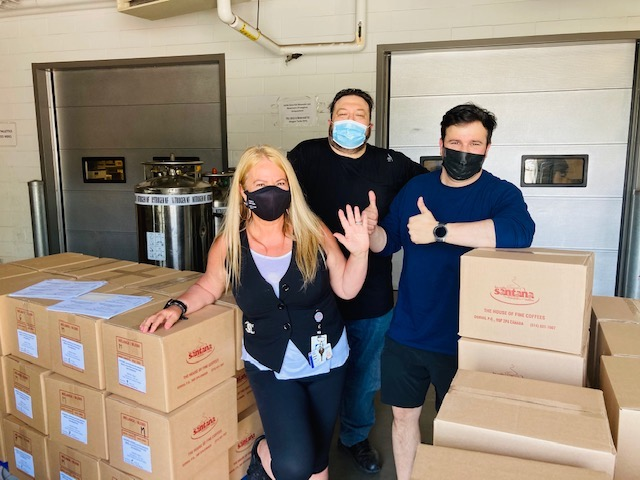 Image of three people posing in masks next to some boxes
