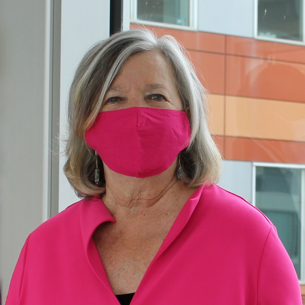 Image of woman wearing a bright pink mask posing for photo