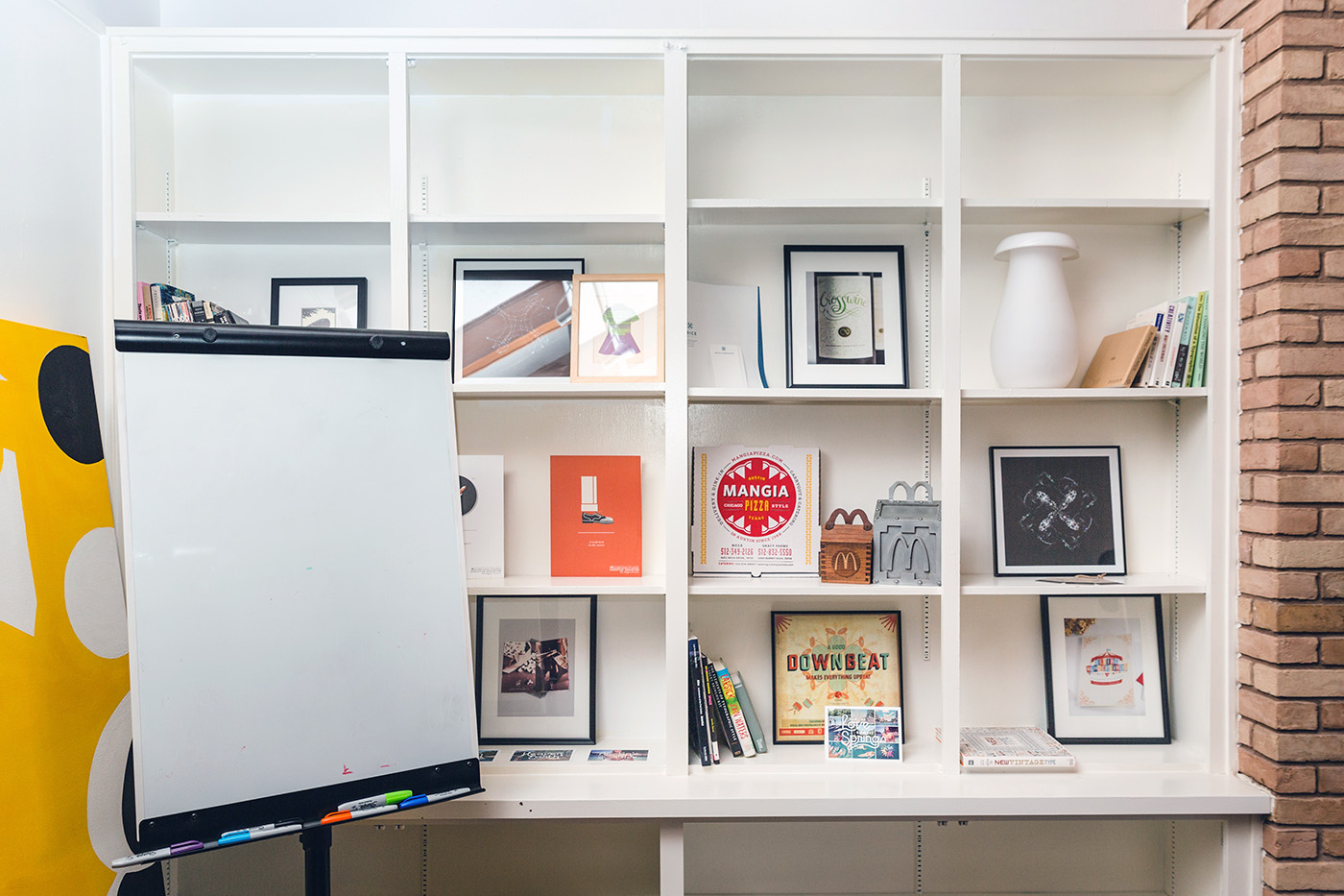 Bookshelves and a whiteboard at the lookthinkmake office.