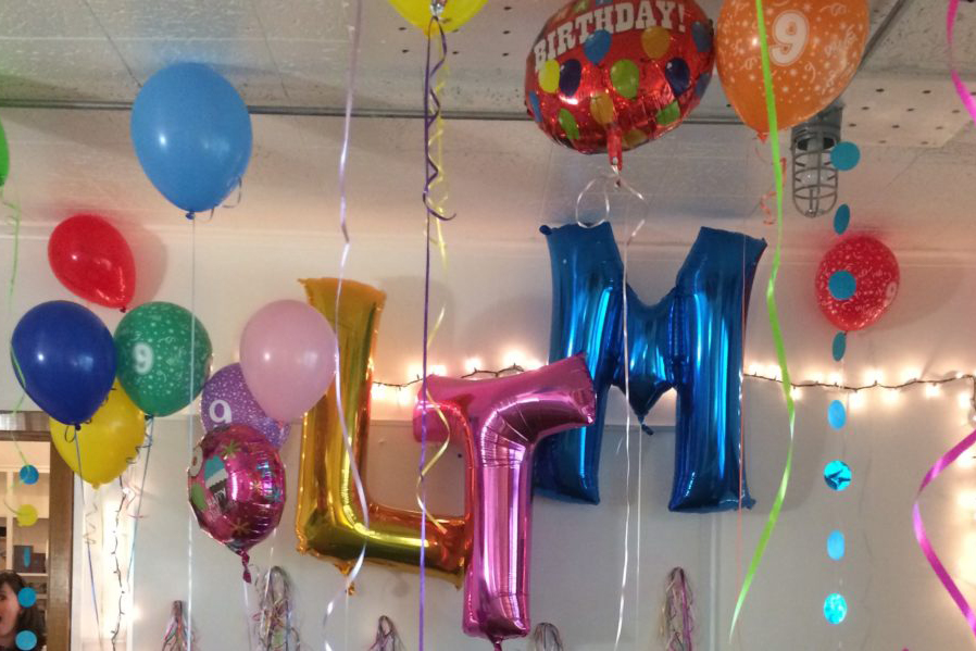 """Ballons spelling out """"LTM"""" during a company birthday party."""