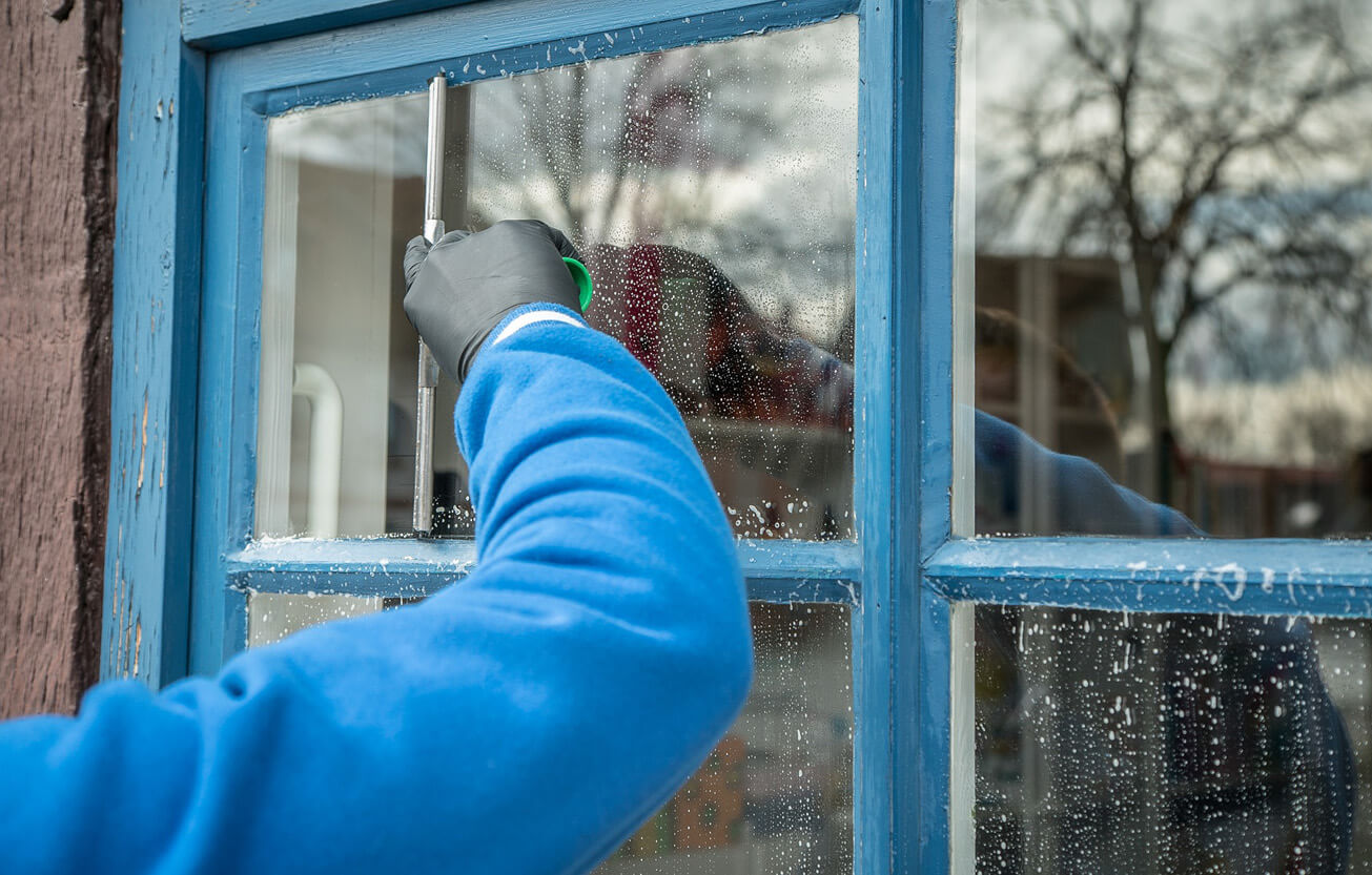 Person performing residential window cleaning services.