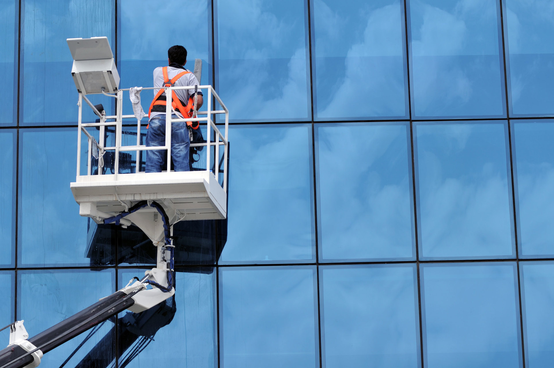 Person cleaning windows on commercial building using lift.