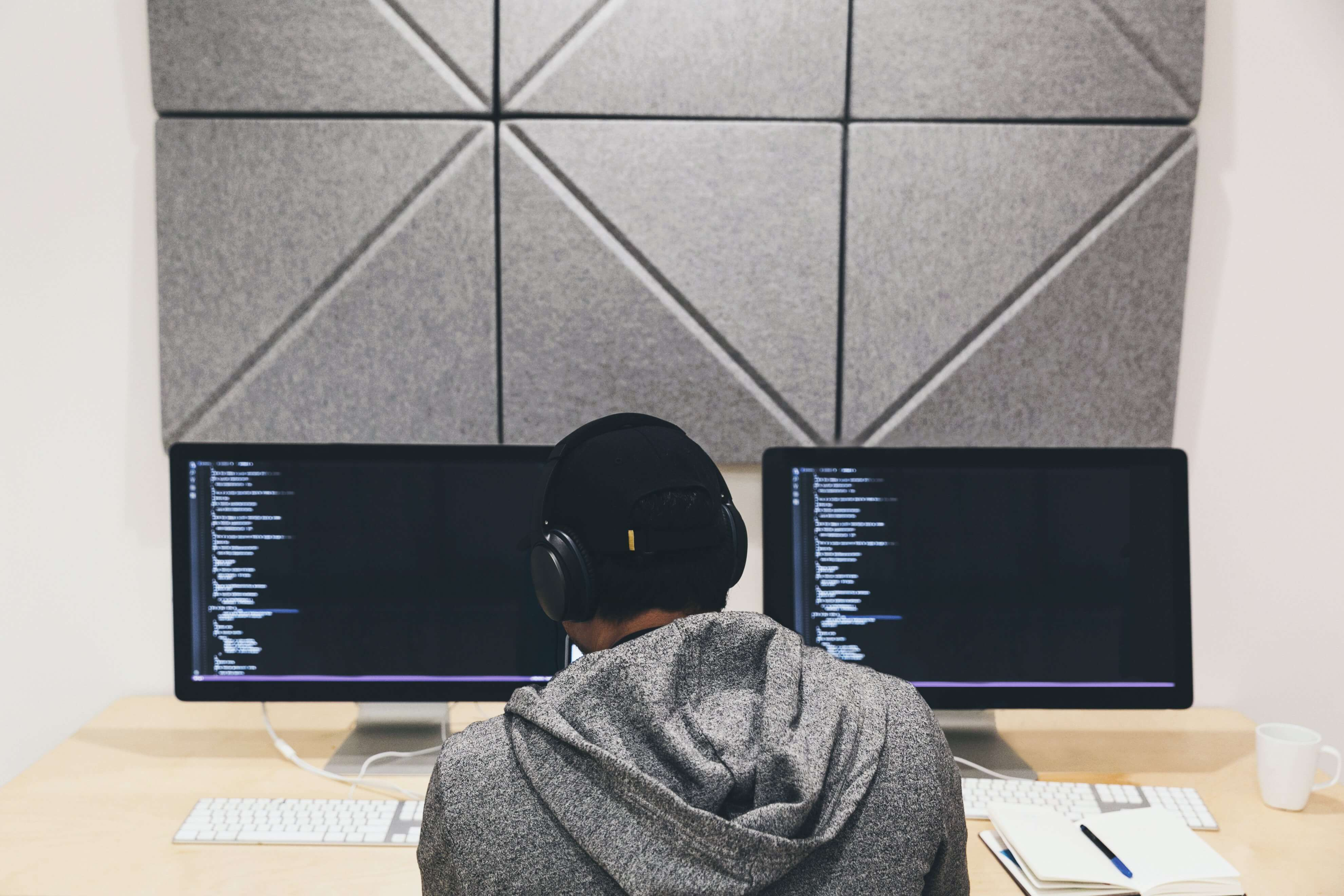 A software developer coding on two monitors