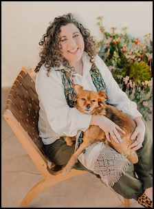 Curly-haired psychic with red dog sits in a chair outdoors