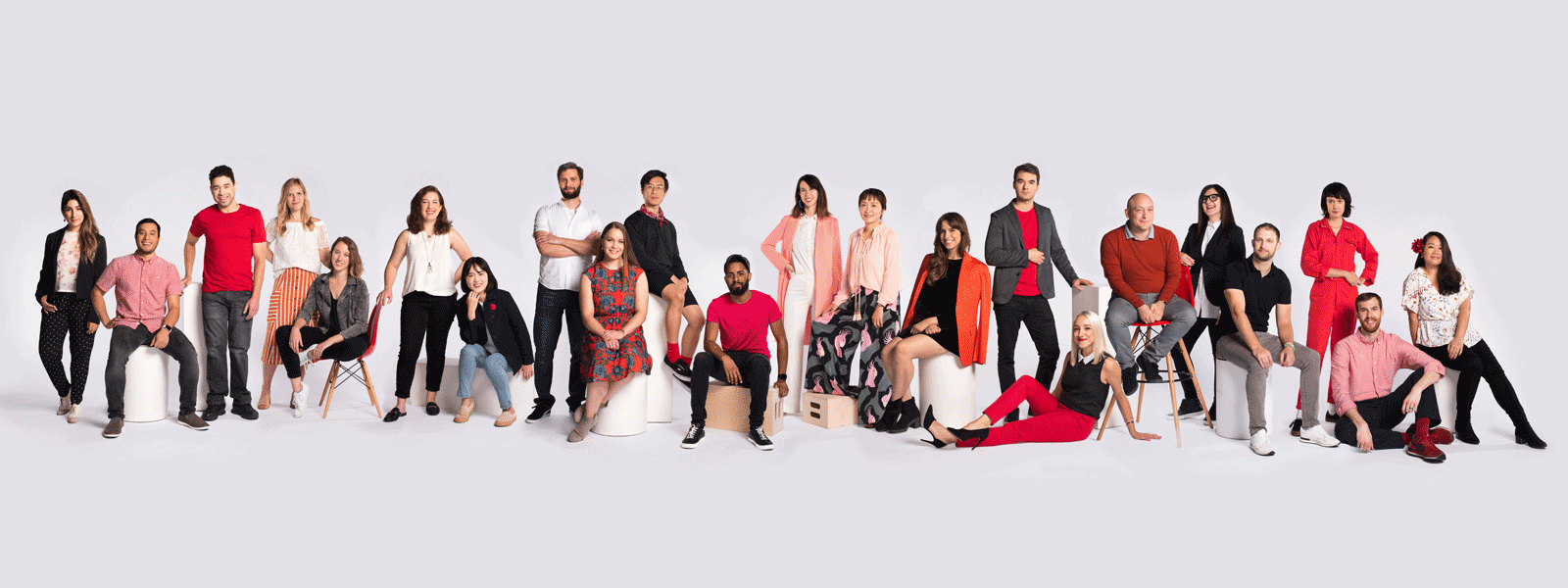 A large group studio photo of the Nickelodeon creative team wearing causal clothes with color pops of the Nickelodeon orange.