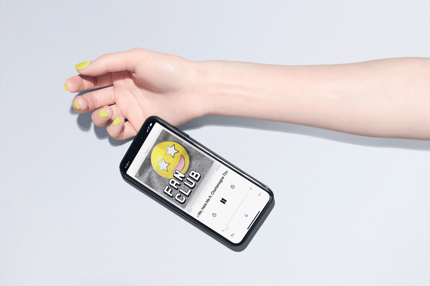 Woman's hand with bright yellow painted nails dropping a smartphone from her hand, displaying the Fan Club podcast identity.