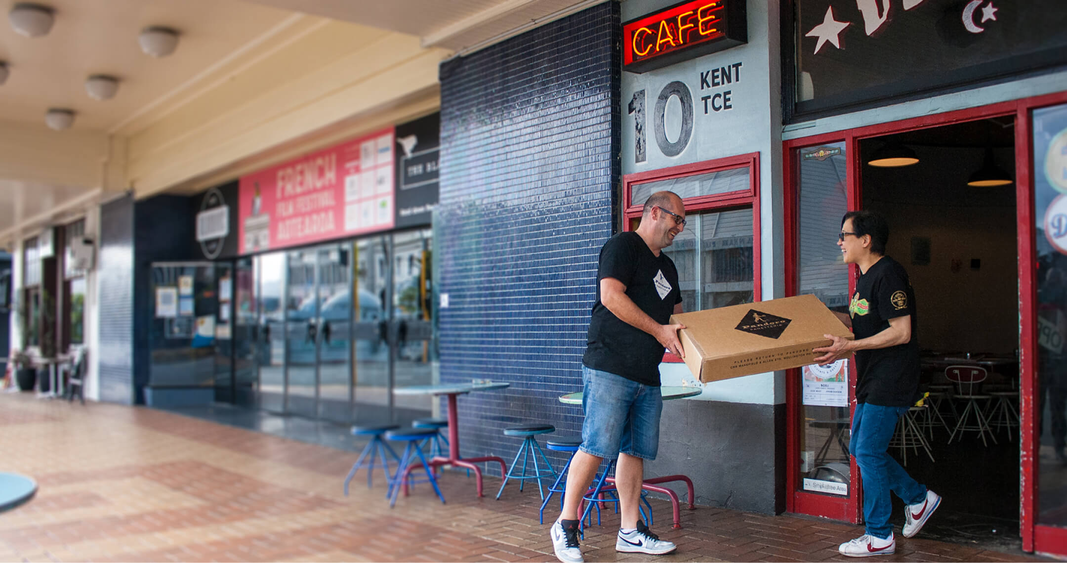 Neville from Pandoro Bakery delivers a box to Sam, the owner of Deluxe Cafe.