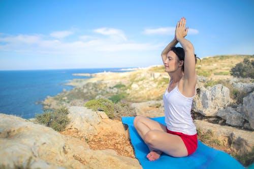 Mujer En Camiseta Blanca Sin Mangas Haciendo Ejercicio De Yoga