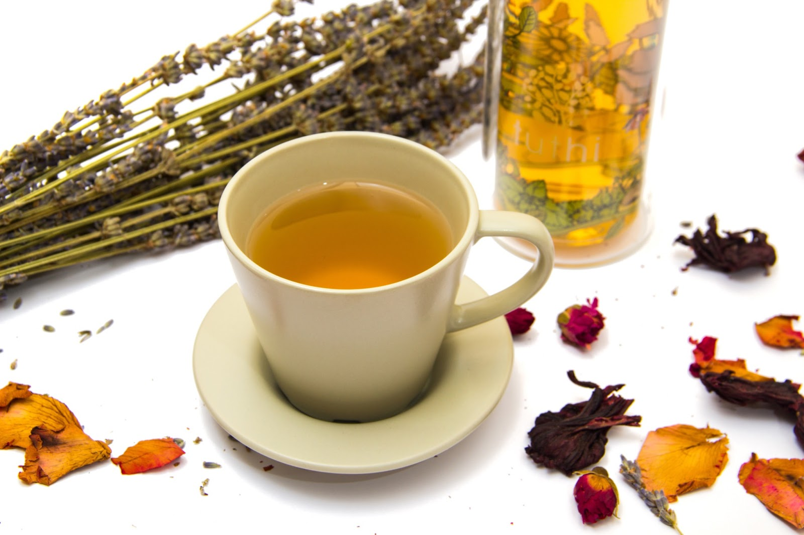 A cup of hot tea is placed in a white mug on a white table, it is surrounded by dried flowers.