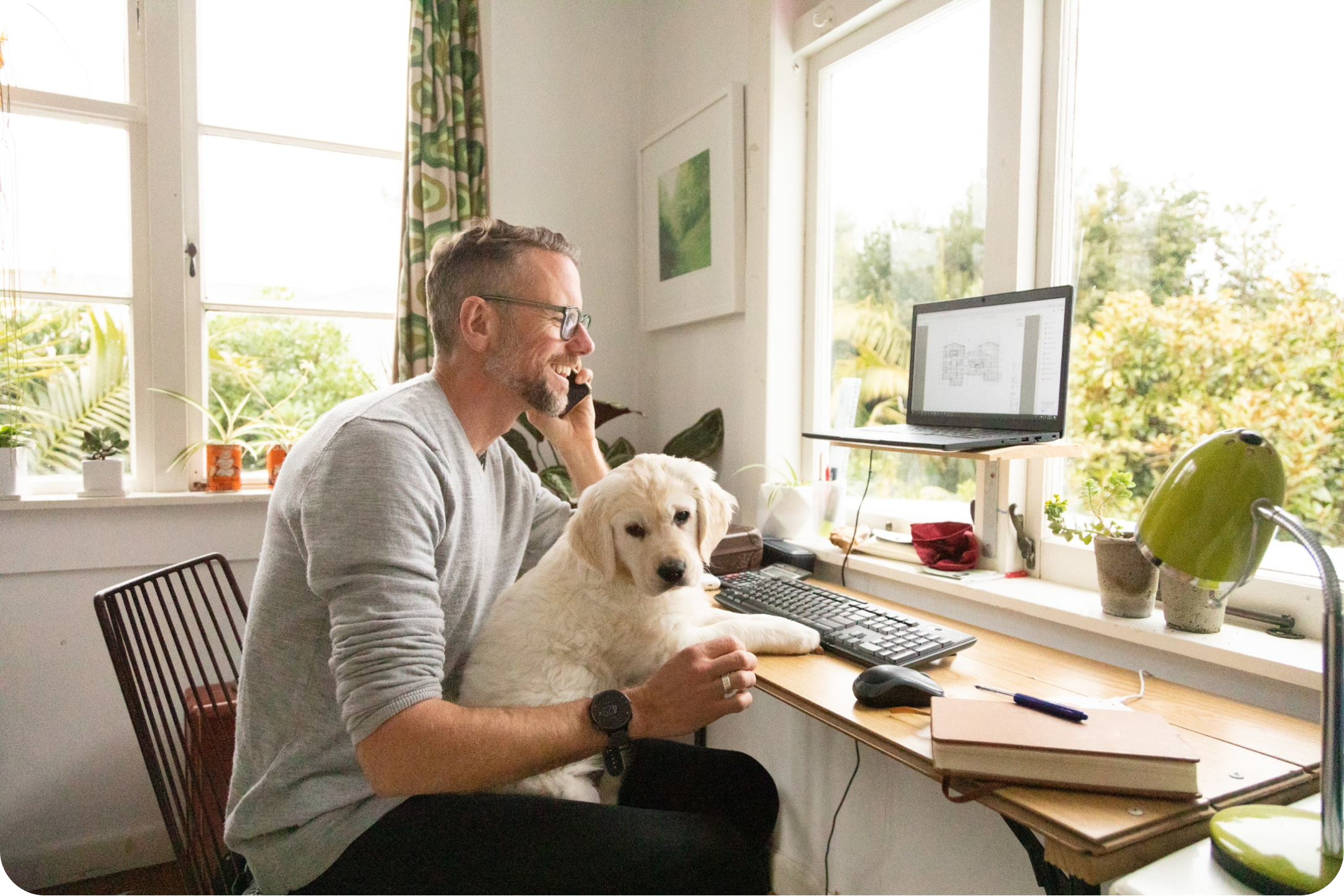 Man and cute dog on computer looking to bills