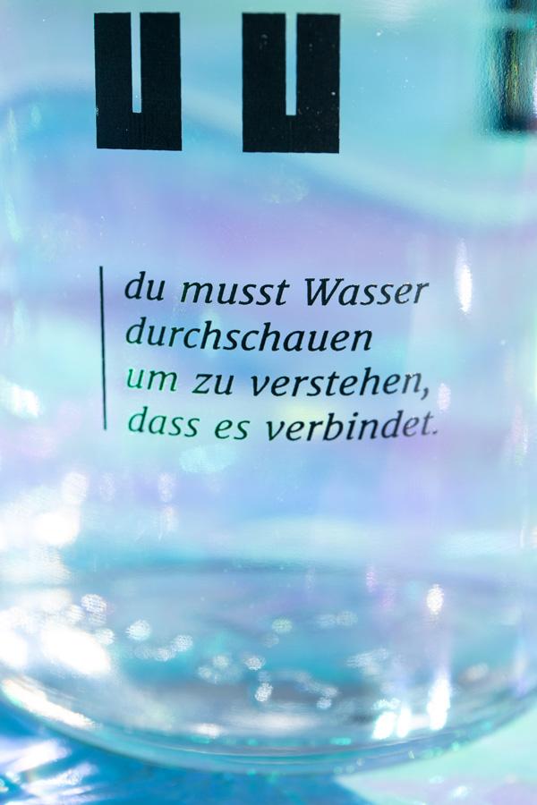 """close up of the bottles quote: """"du musst Wasser durchschauen um zu verstehen, dass es verbindet"""""""