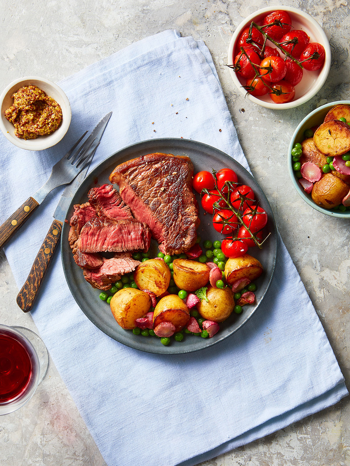 Rump steak served medium rare with gilled cherry tomatoes and new potato salad