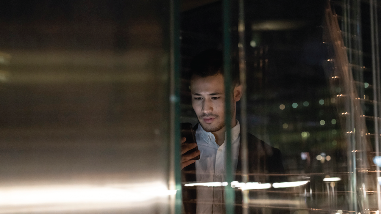 A man looking at his phone with concern