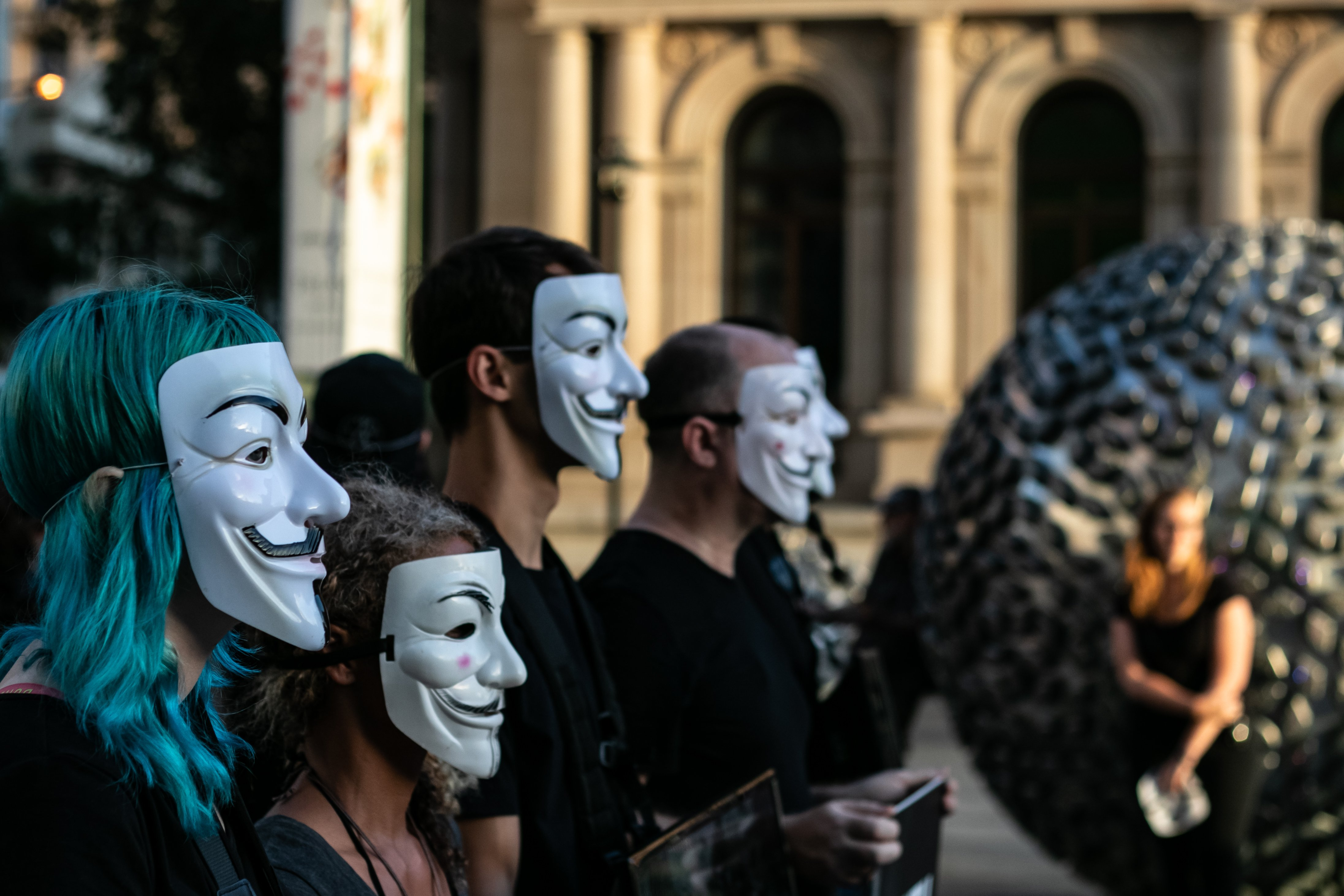 A group of people standing wearing Guy Fawkes mask and black tshirt