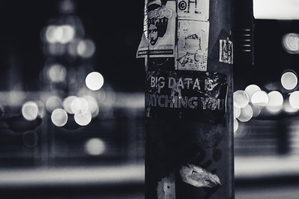 A black and white image with a pillar and multiple posters on it saying big data is watching you