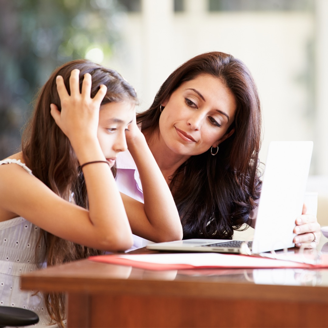 A mother with a young daughter and a laptop in front of them. Mother guiding and helping daughter who looks upset while looking at her laptop screen.