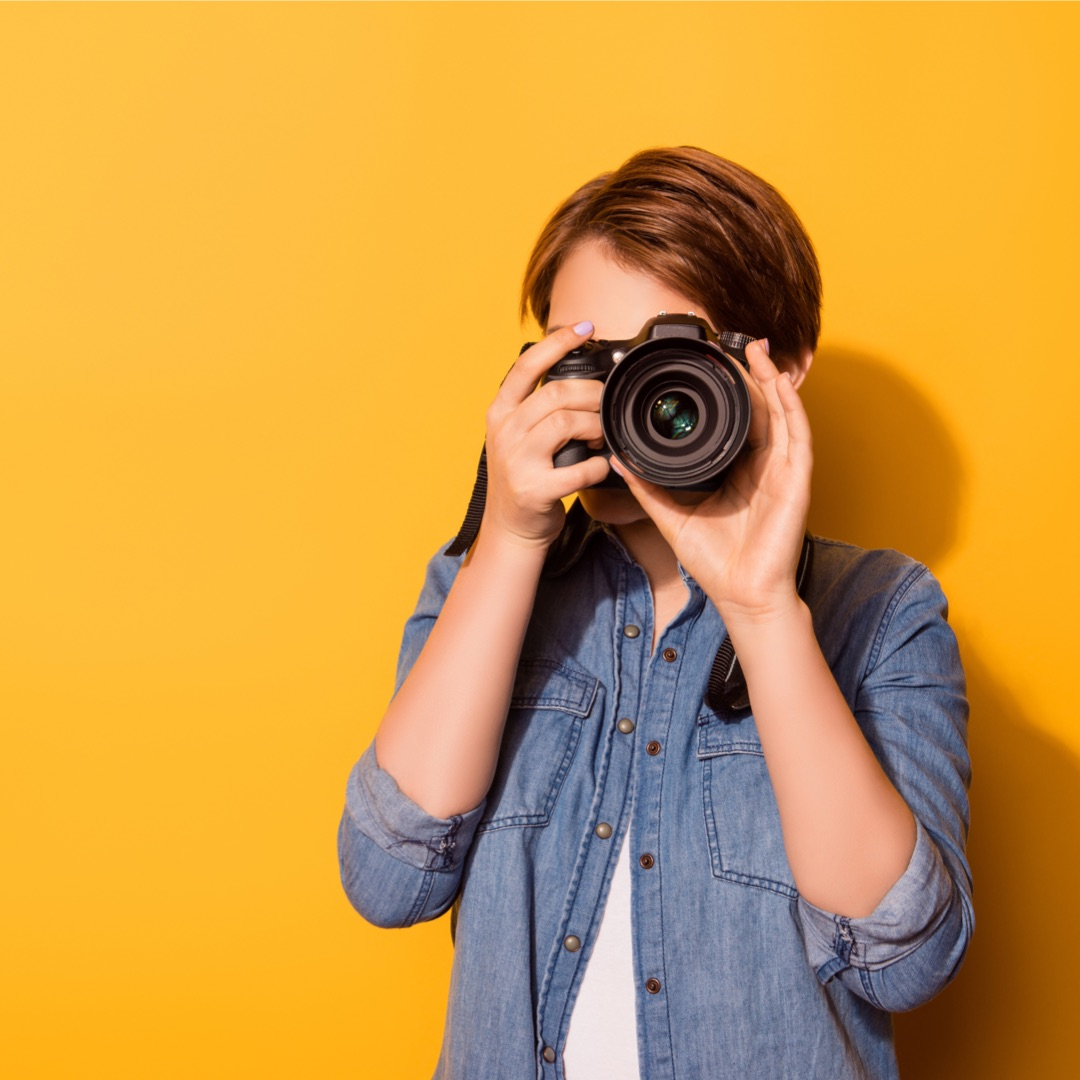 A woman photographer with yellow background taking a photo