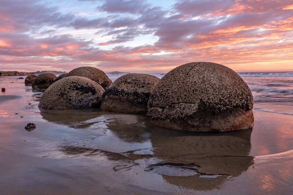 A beautiful photo of nature with rounded rock formation near wet sand on a beach in New Zealand.