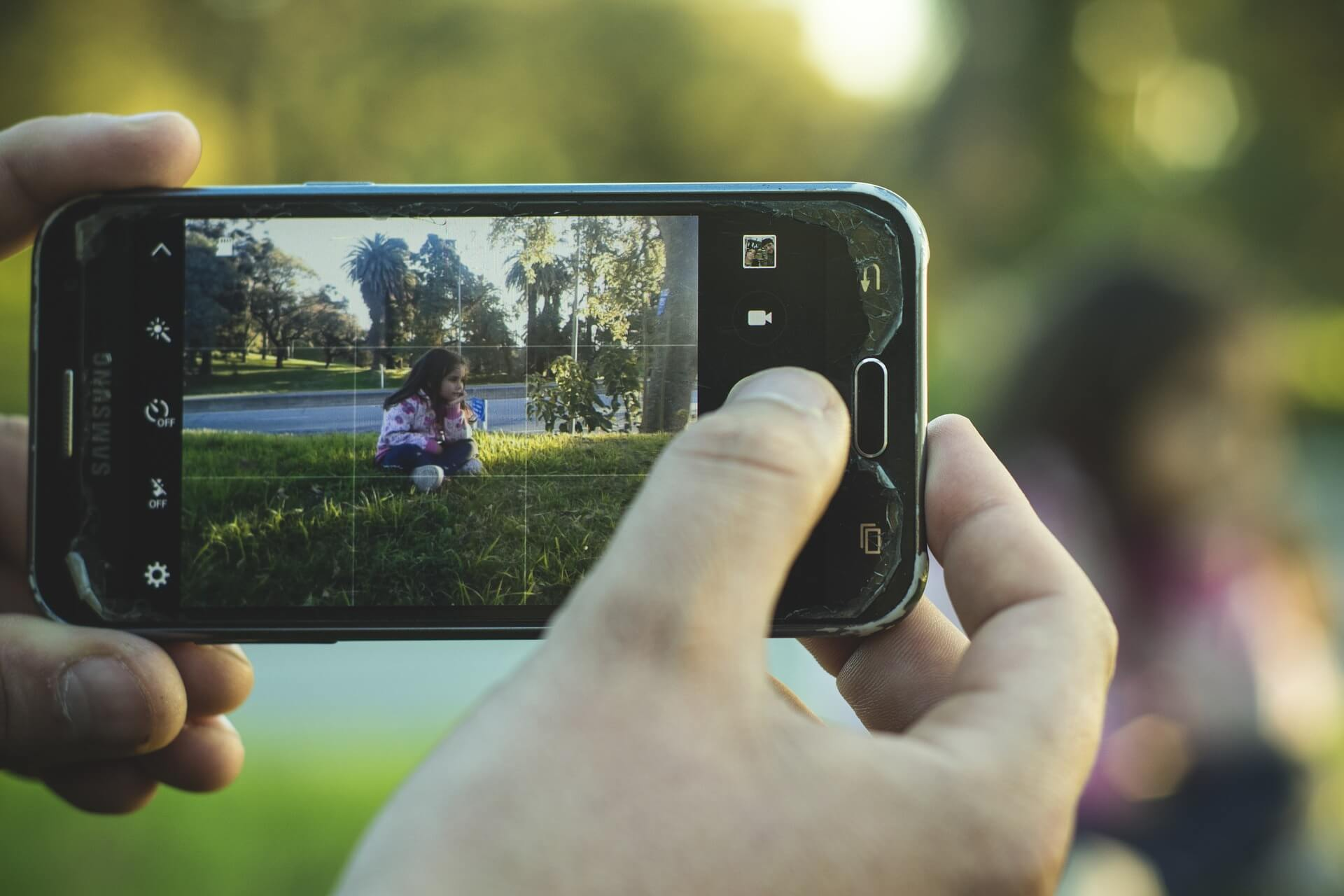 A person holding a phone and taking photo of their kid in the park