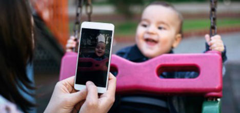 A person holding a phone and taking a photo of their smiling toddler on a pink swing