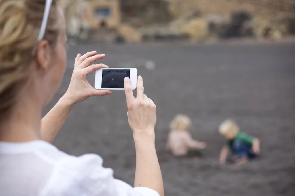 A person taking photo of their 2 kids playing in the sand