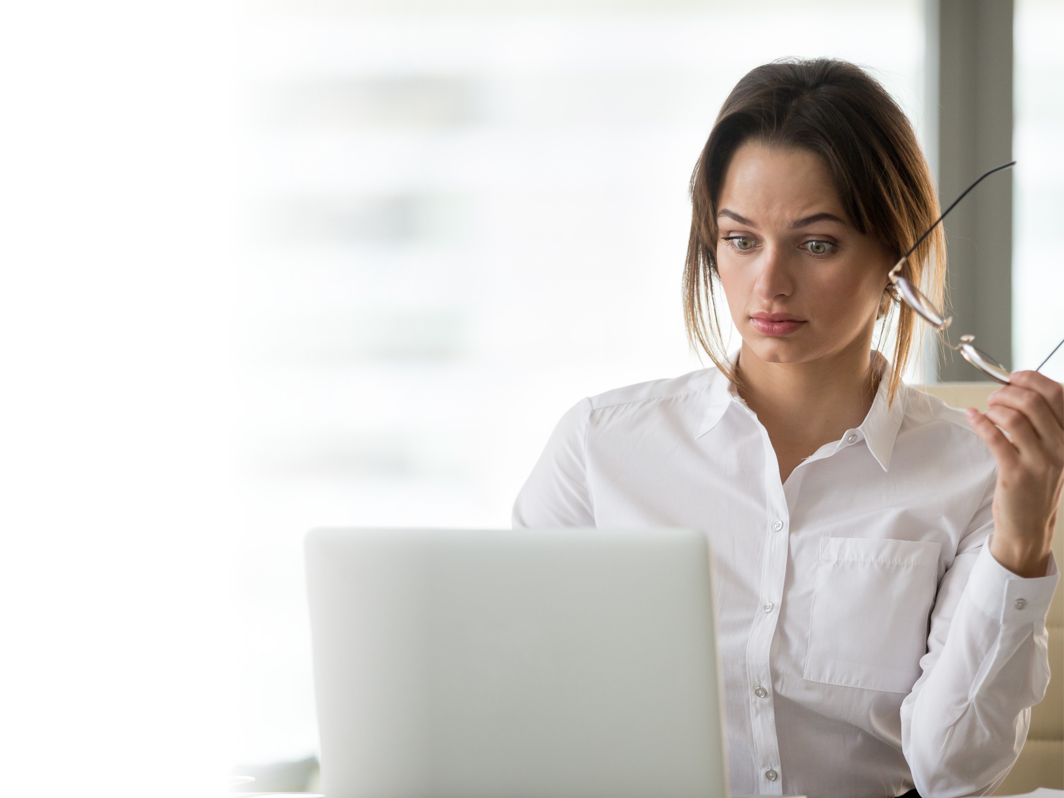 A woman is shocked looking at her computer.