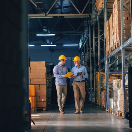 Two warehouse employees standing and looking at documentation.