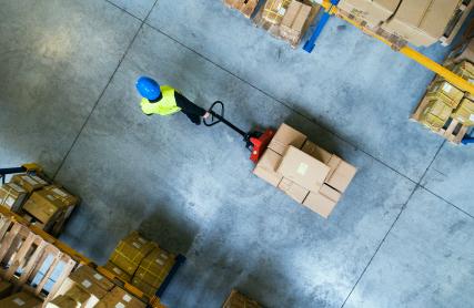 Worker pulls a pallet truck