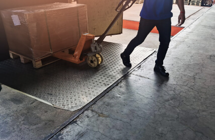 Worker driving forklift loading shipment carton boxes