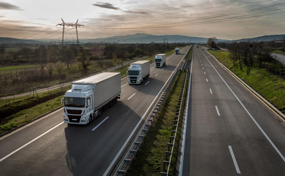 A caravan of trucks lining up on a suburban highway