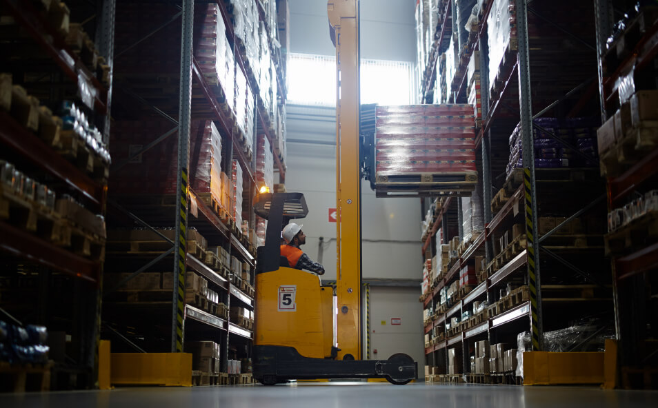 Side view portrait of warehouse worker using forklift truck to load pallets with boxes on high rack