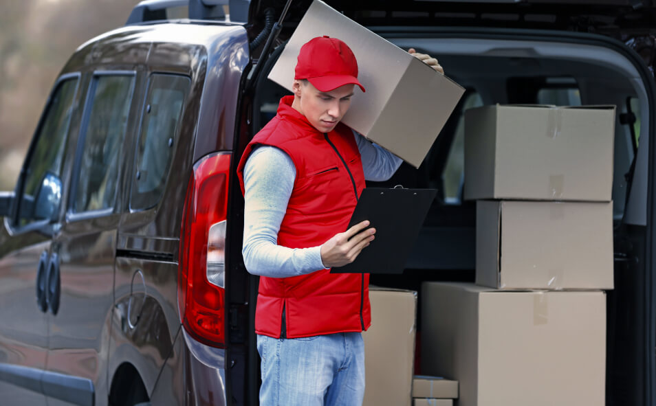 delivery man standing near the car with boxes and packages