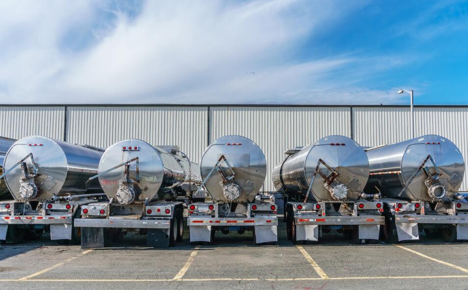 Row shiny metal tanker trucks