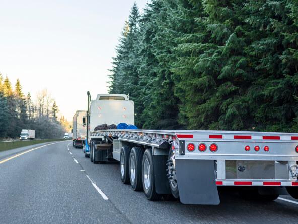 powerful semi truck with empty light weight aluminum flat bed semi trailer