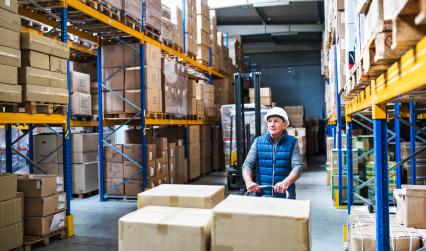 Senior male warehouse worker pulling a pallet truck